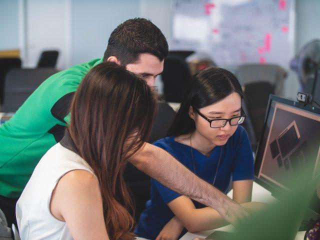 un mec qui montre du doigt un écran et 2 femmes qui apprennent ce qu'il montre